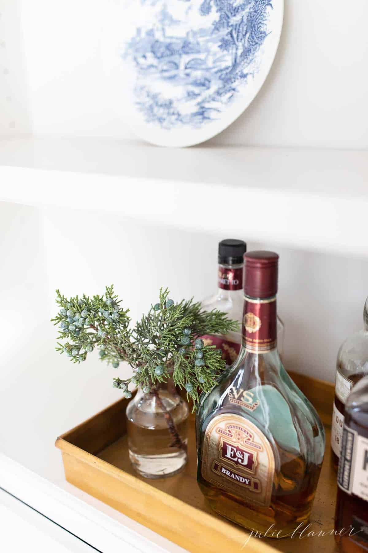 juniper in bud vase on tray with liquor
