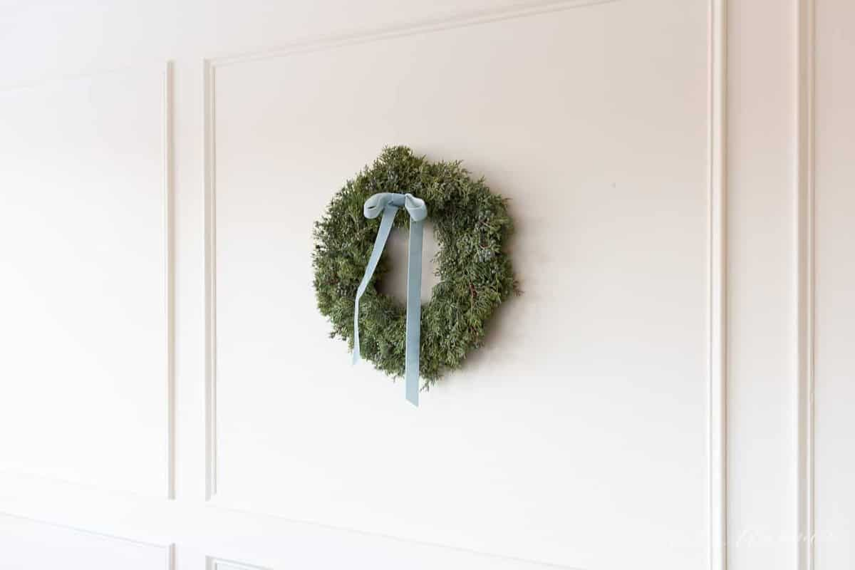 juniper christmas wreath with velvet ribbon hanging on wall