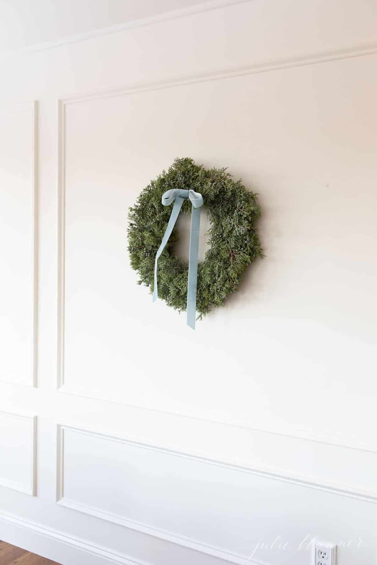 juniper wreath with blue velvet ribbon in cream breakfast nook