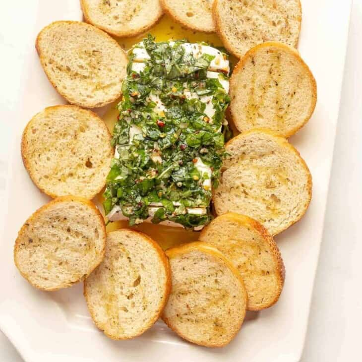 An herb cream cheese recipe surrounded by crostini on a white platter.