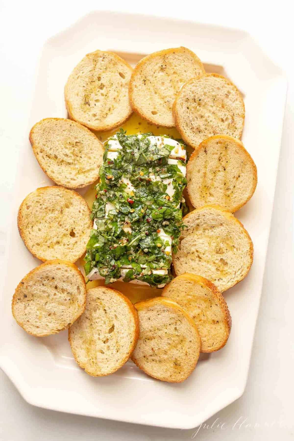 Marinated cheese surrounded by crostini on a white platter.
