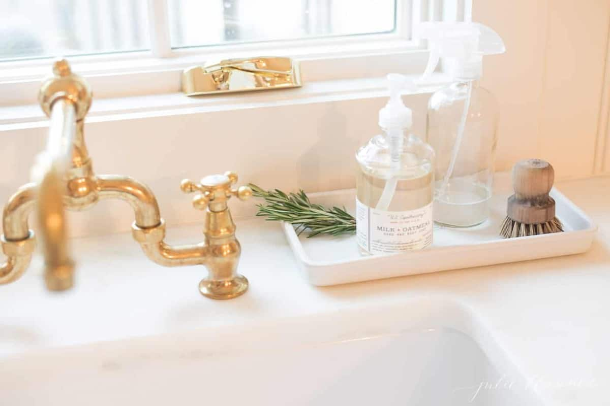 rosemary on tray with soap next to brass faucet