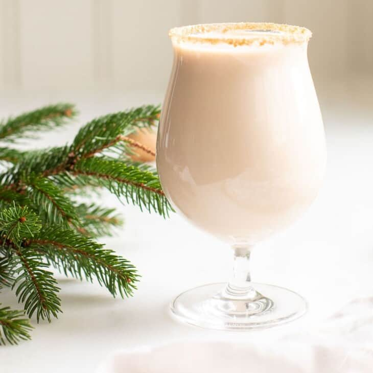 A clear glass with an oatmeal cookie shot, hazelnuts and greenery to the side.