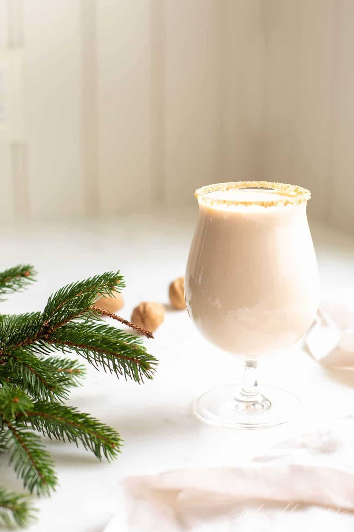 A clear glass with an oatmeal cookie drink, hazelnuts and greenery to the side.