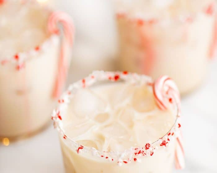 three clear glasses of peppermint cocktails, garnished with a candy cane.