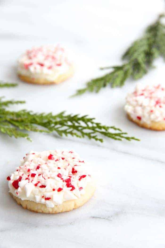 Marble surface, greenery tucked between three peppermint desserts, peppermint frosted sugar cookies.