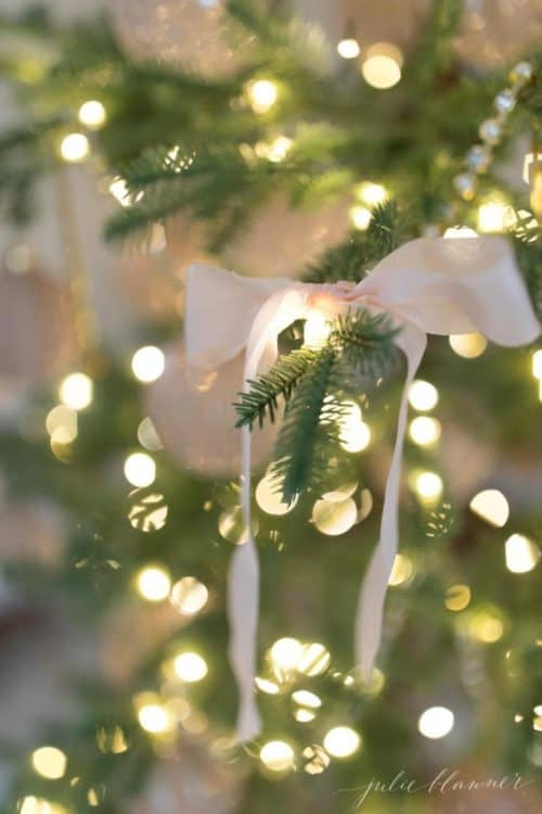 Close-up shot of Christmas tree with pink bow.