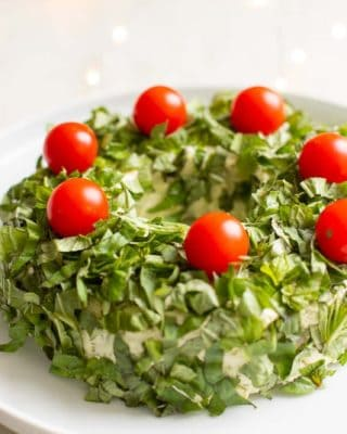 White marble surface with a white platter, featuring a pesto cheese appetizer in the shape of a wreath covered in basil, cheery tomatoes on top for ornaments.
