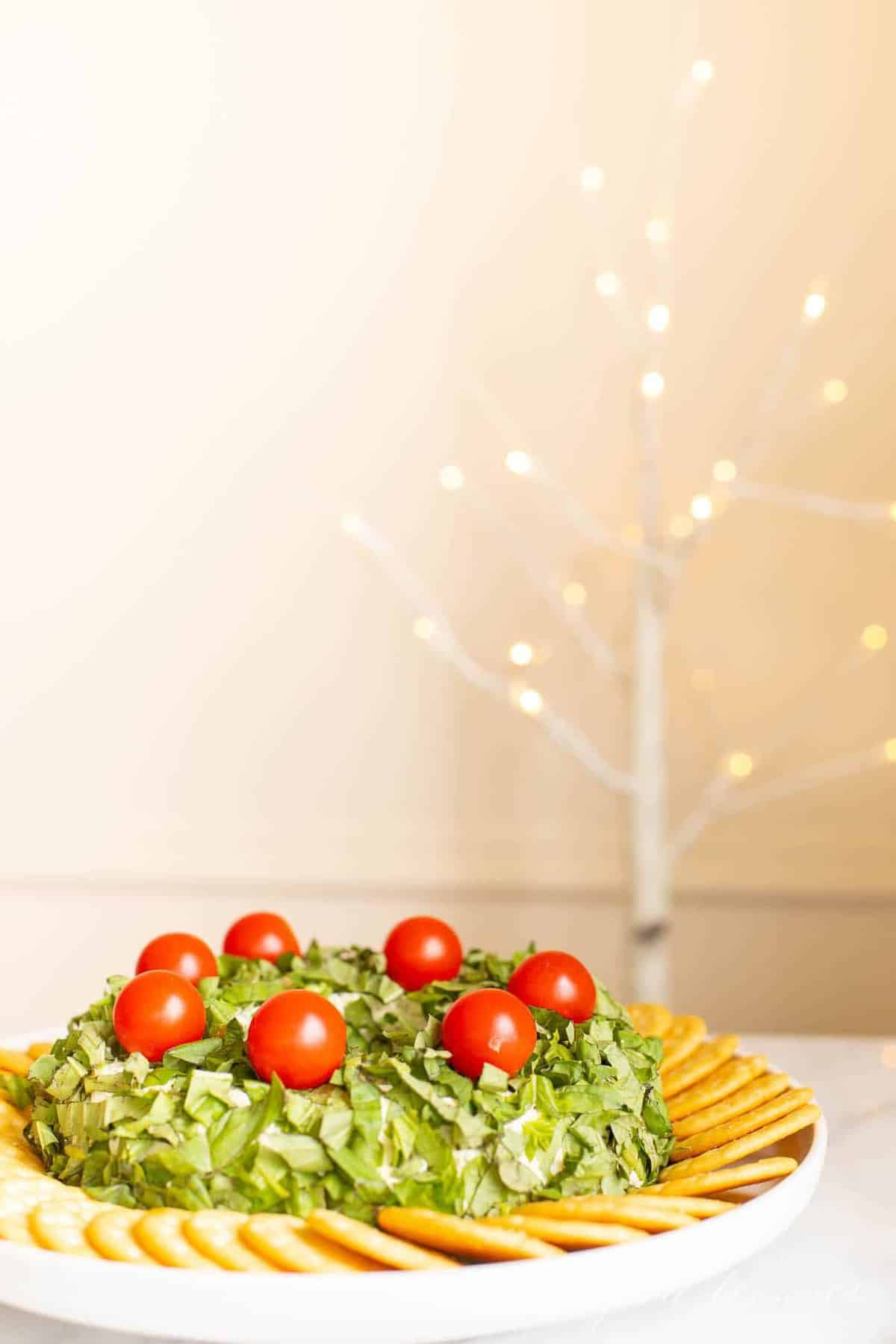 A pesto cheeseball Christmas wreath appetizer surrounded by crackers on a platter. Sparkling tree in the background.