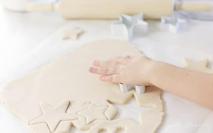 kid cutting out salt dough with cookie cutters