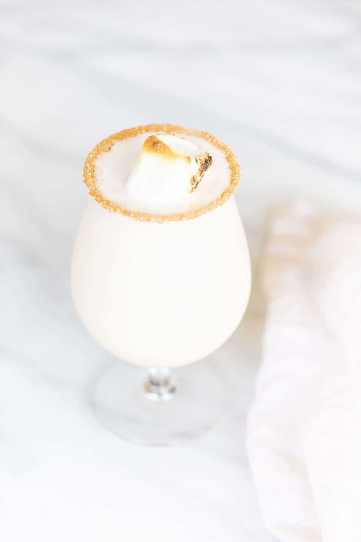A white surface with a clear glass filled with amaretto flavor snowball cocktail recipe, toasted marshmallow as garnish.
