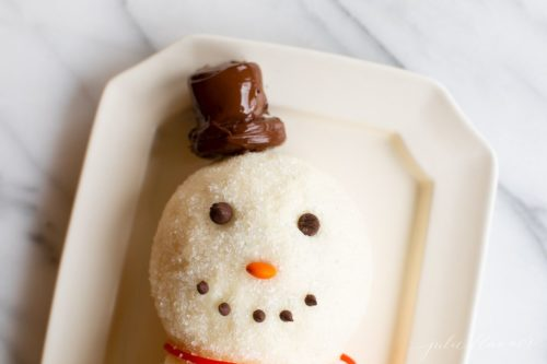 White surface, snowman cheeseball on a platter, chocolate chip smile, chocolate marshmallow hat.