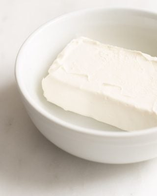White bowl with a block of cream cheese inside.