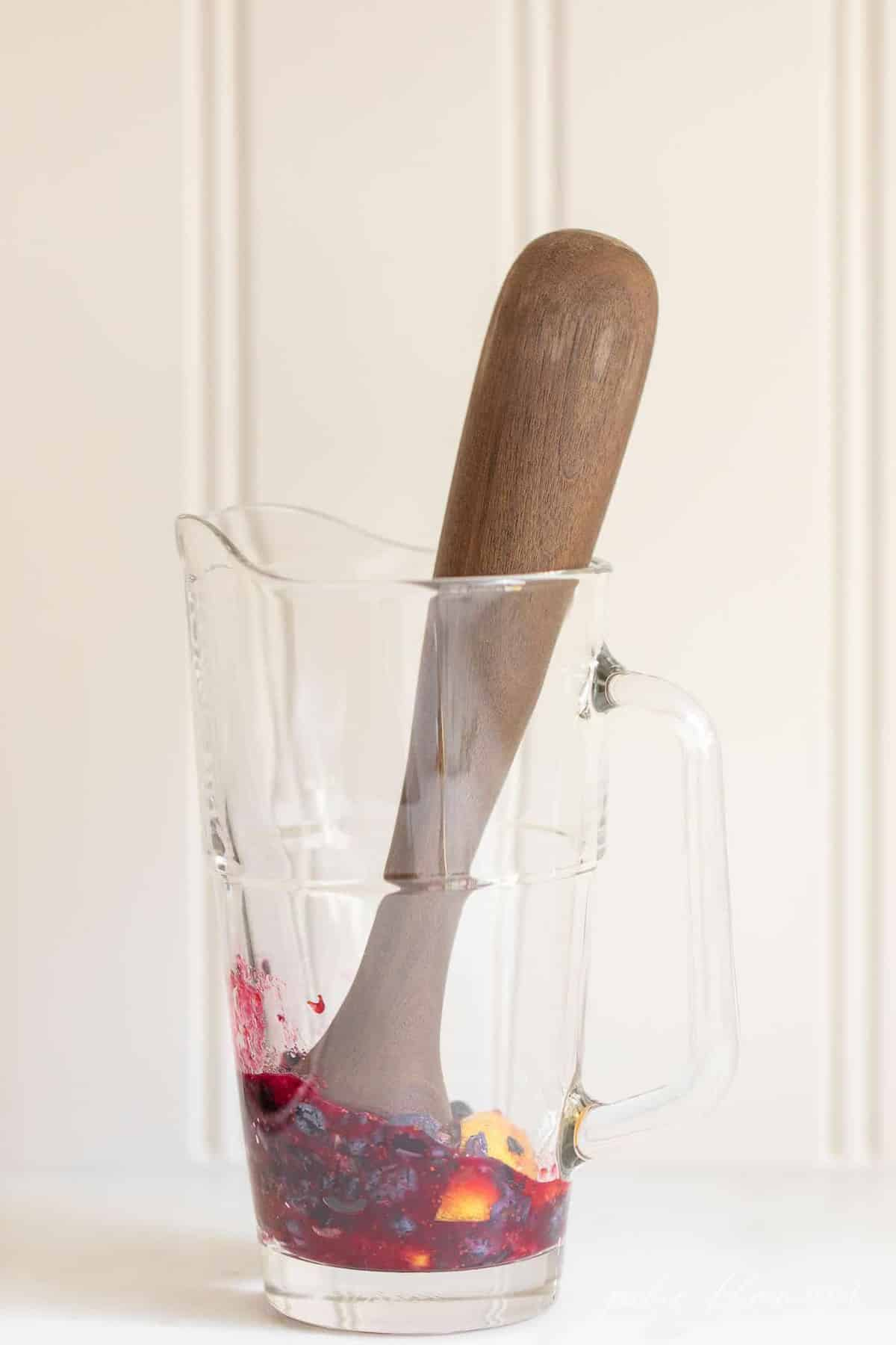 Clear pitcher, white surface, muddler inside smashing fruit for a bourbon smash recipe.