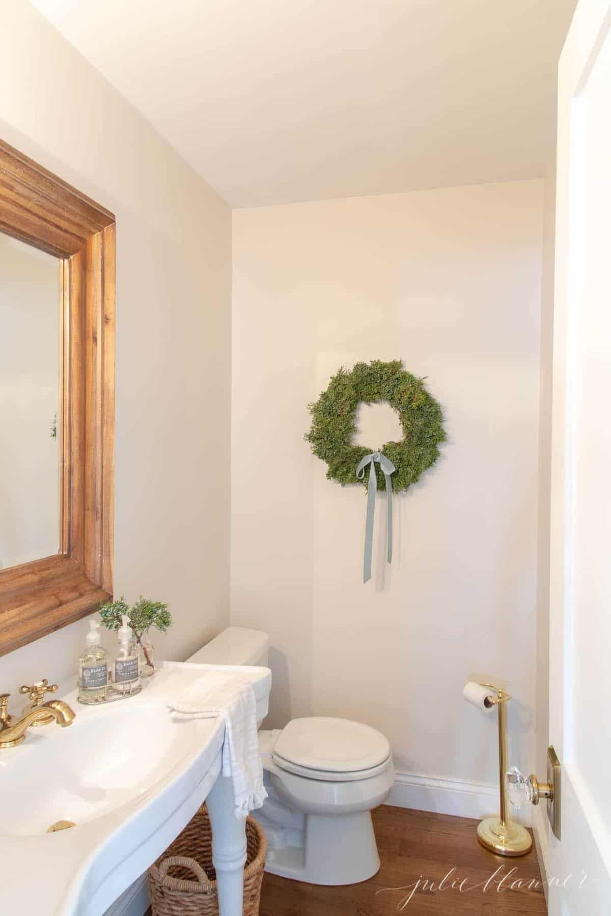 juniper wreath in bathroom with wood mirro and parisian sink