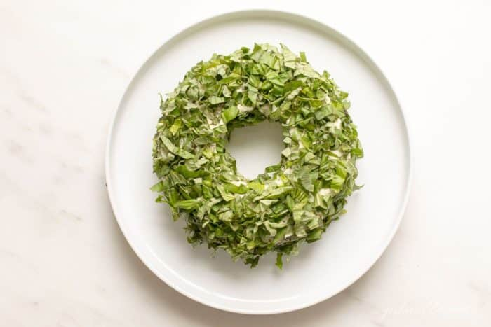 White marble surface with a white platter, featuring a pesto cheese appetizer in the shape of a wreath covered in basil.