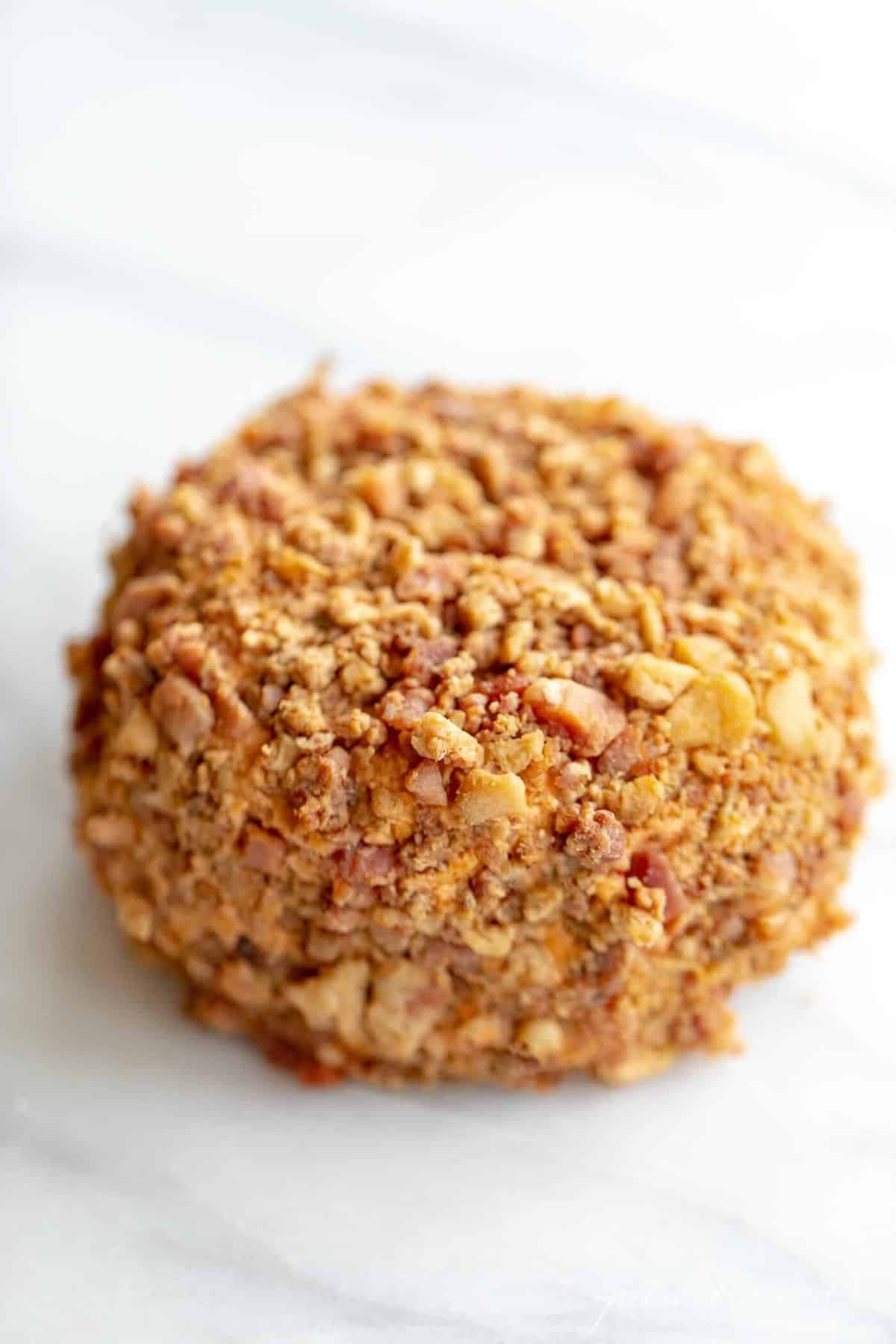 Marble counter top with a bacon covered cheese ball.