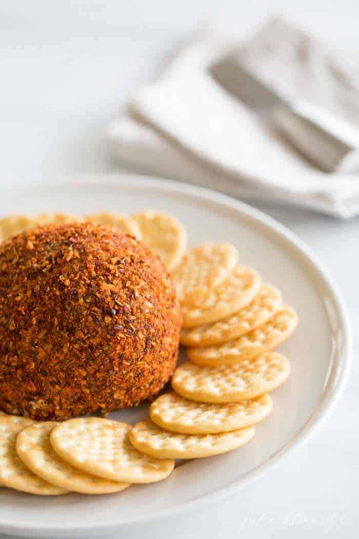 A spice covered cheeseball on a platter, crackers surrounding.