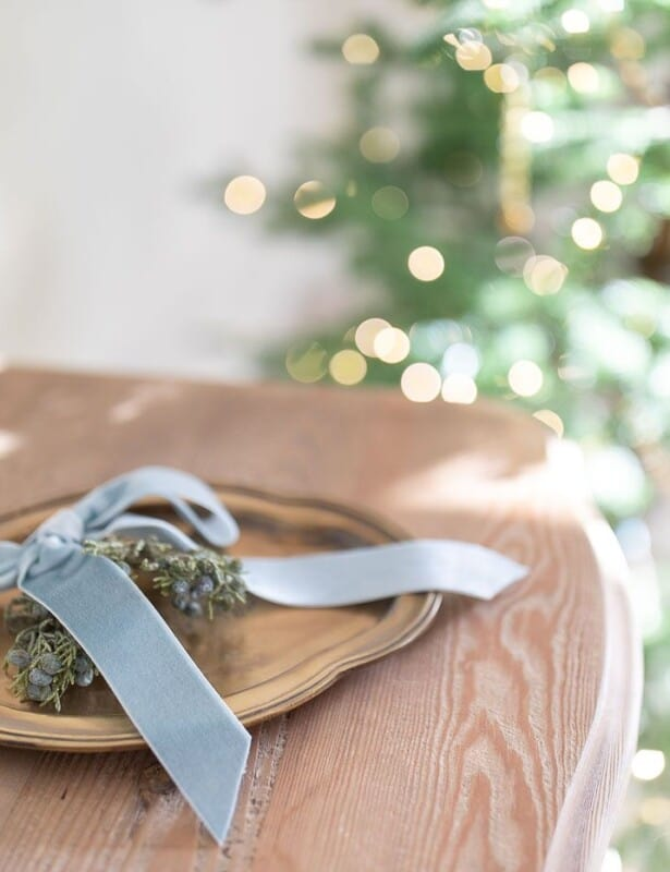 Close up of a wood dresser with a tray of holiday greenery.