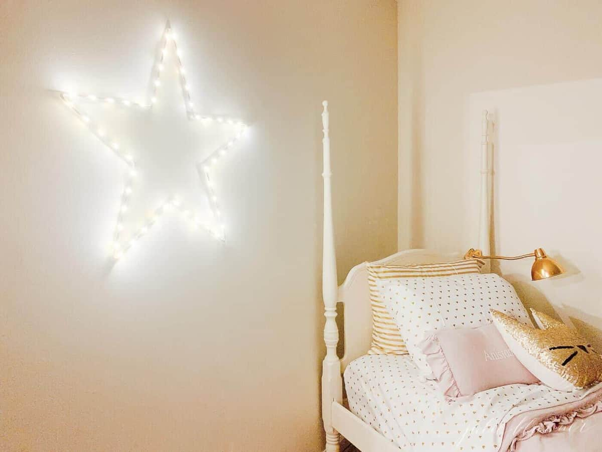 A bed in a room with light up star