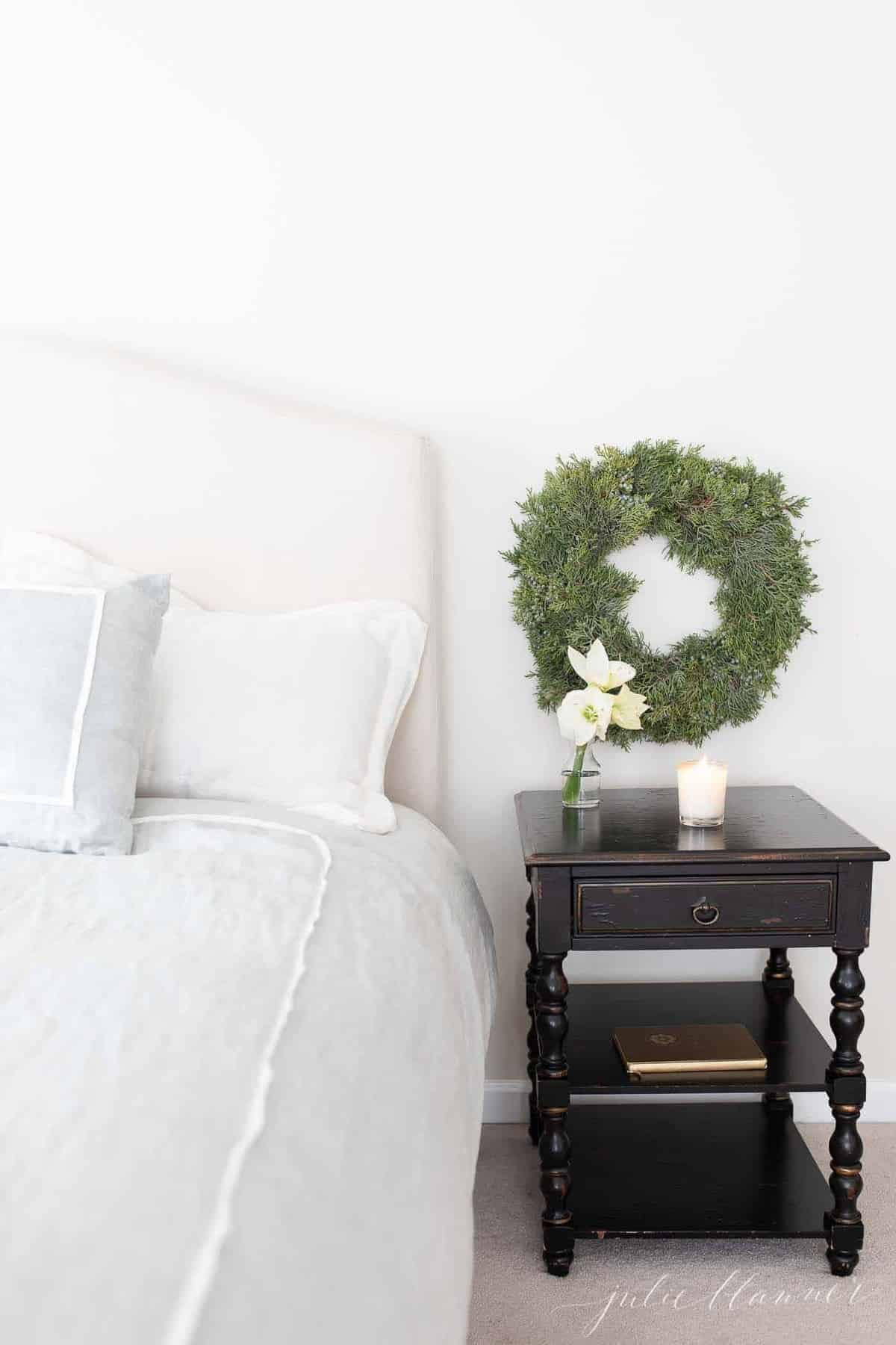 A soft blue and white bed with a black nightstand and Christmas wreath above.