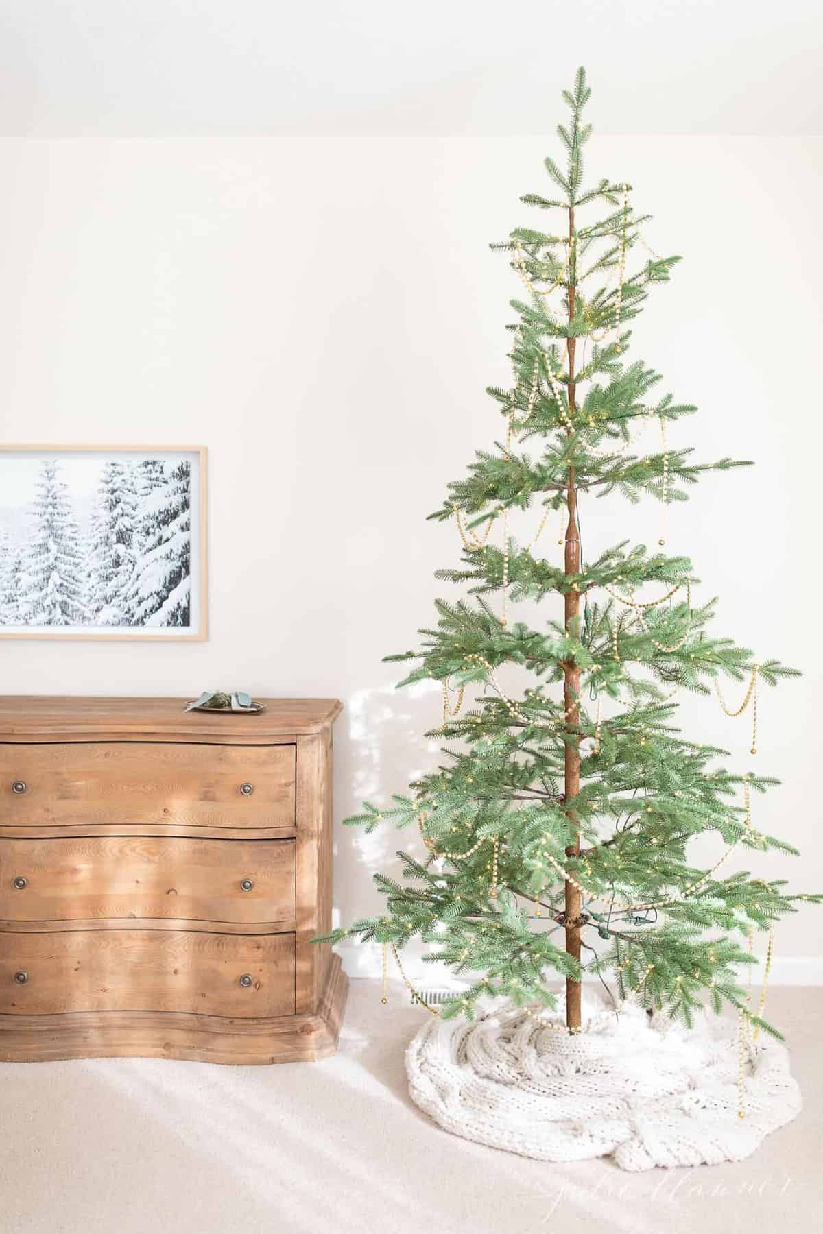 Christmas bedroom decor with a pretty tree, soft wood dresser and art tv.