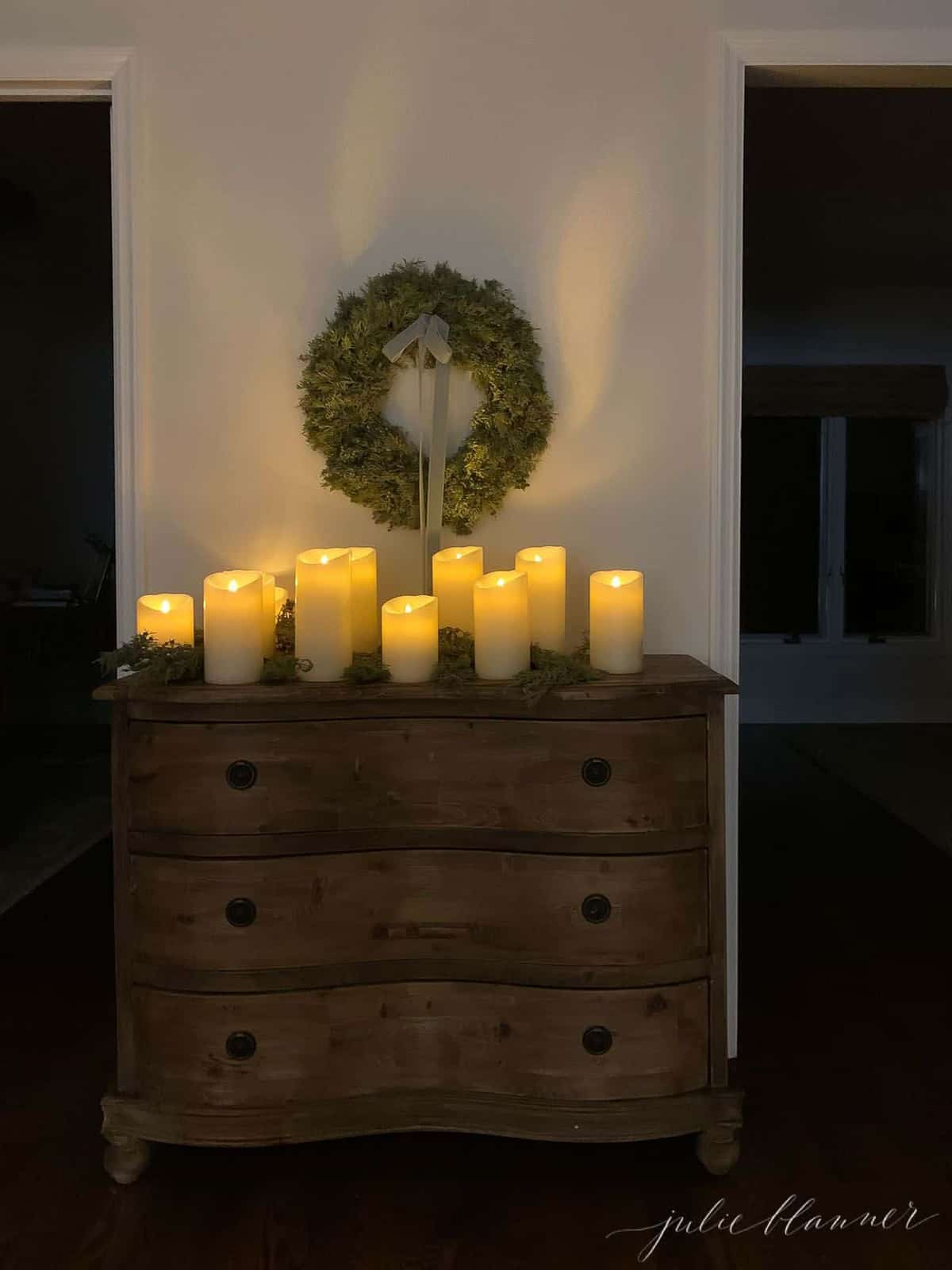 Entryway at night, candles and evergreen on a console table, wreath above.