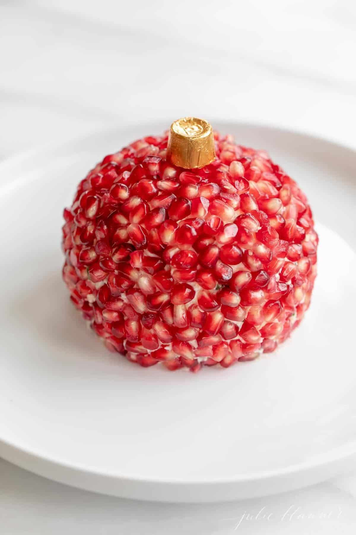 A white platter featuring a holiday cheese ball covered in pomegranate anis.