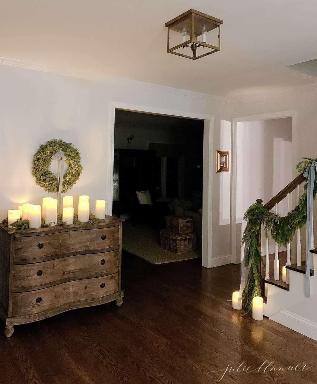 Darkly lit entryway at night, candles and evergreens decorating for Christmas.