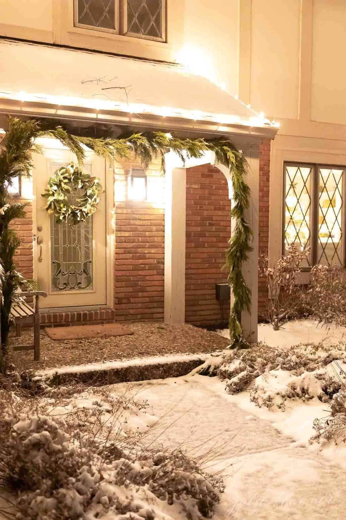 Exterior of a home, snow on the ground and greenery garland on posts for Christmas.