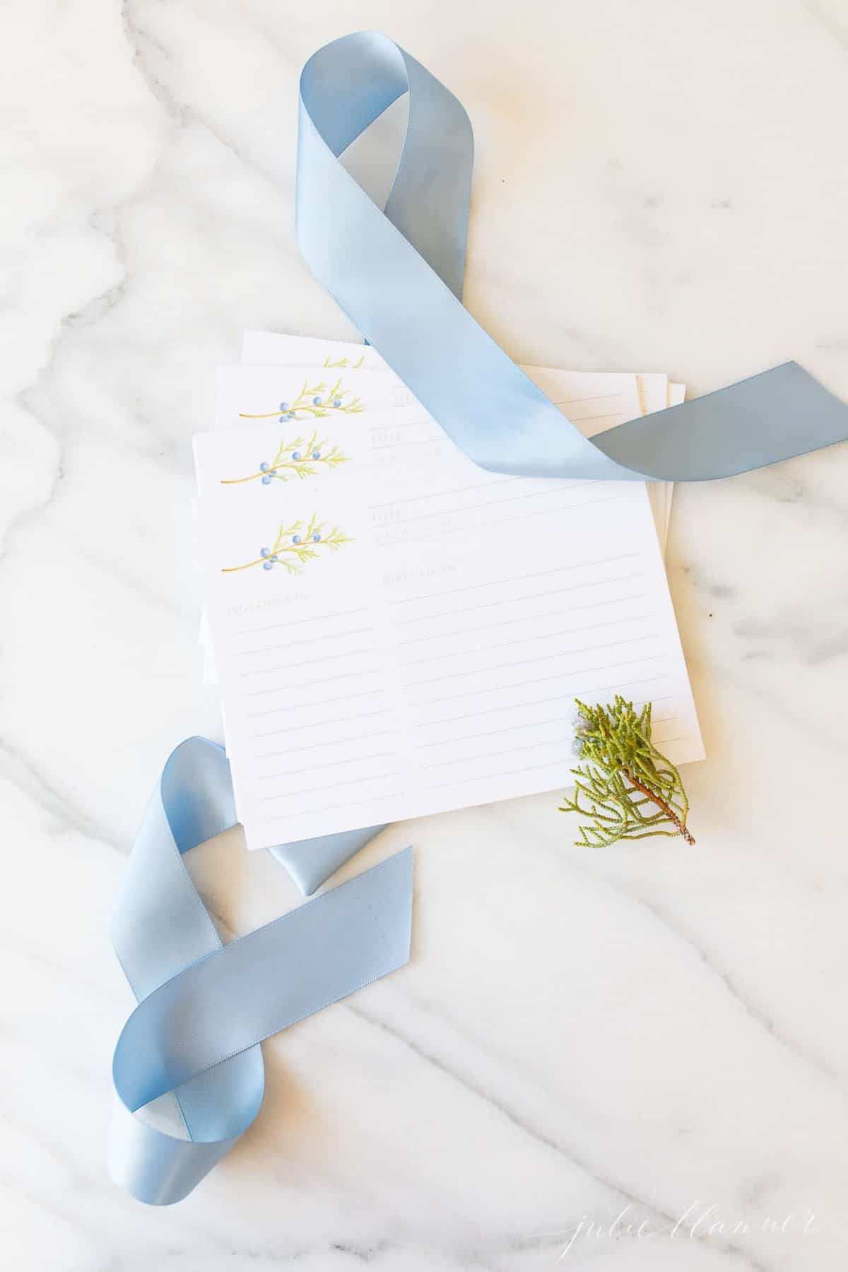 A marble surface with pretty white recipe cards and a blue ribbon accent.