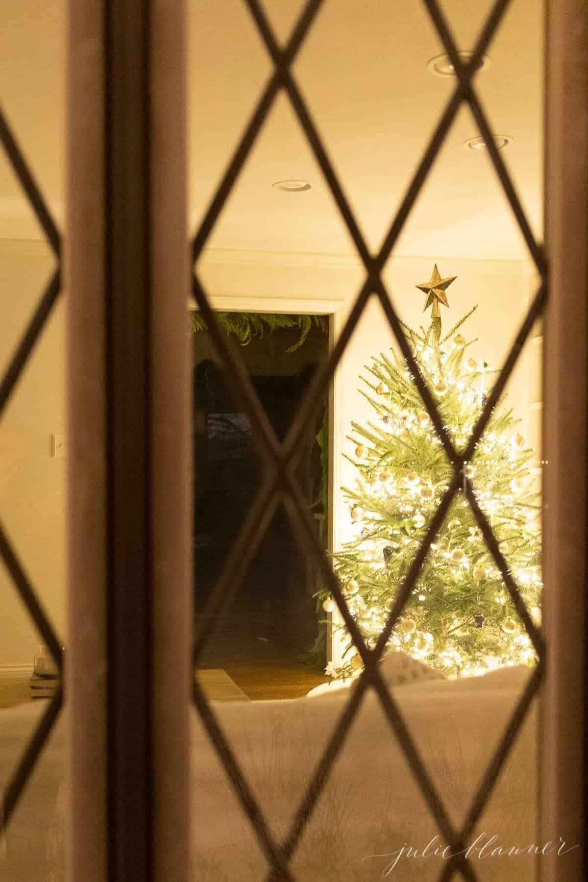 Looking from outside into a living room Christmas tree scene, at night.
