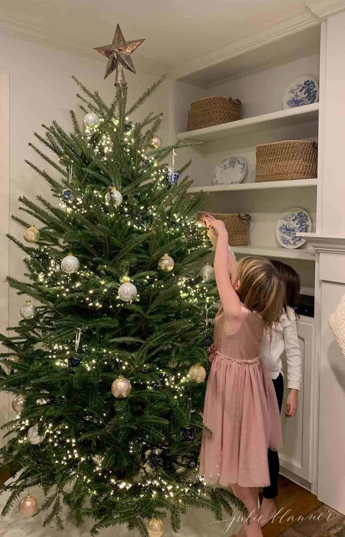 Little girls decorating a Christmas tree