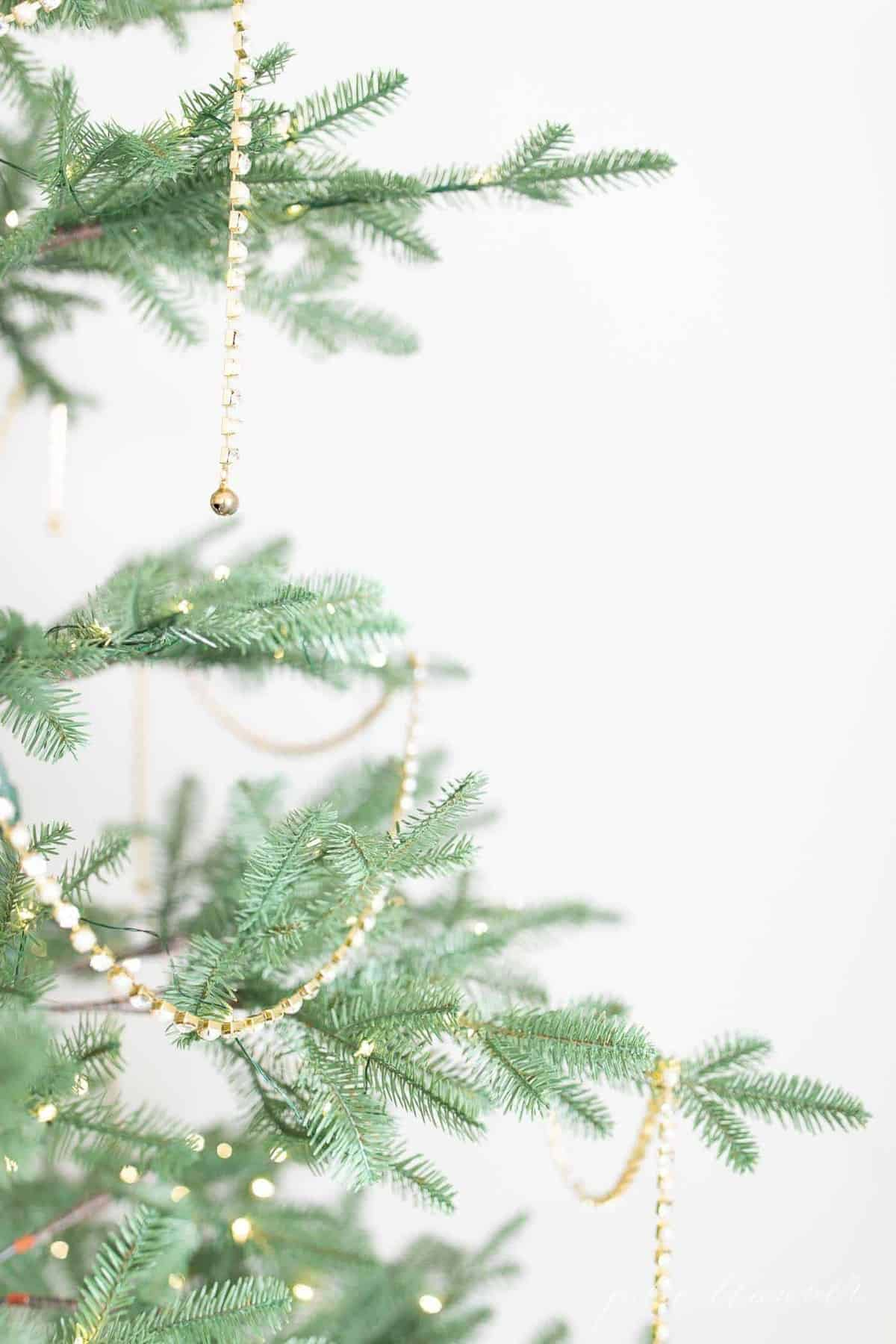 Close up shot of a Christmas tree draped with sparkling beaded garland.