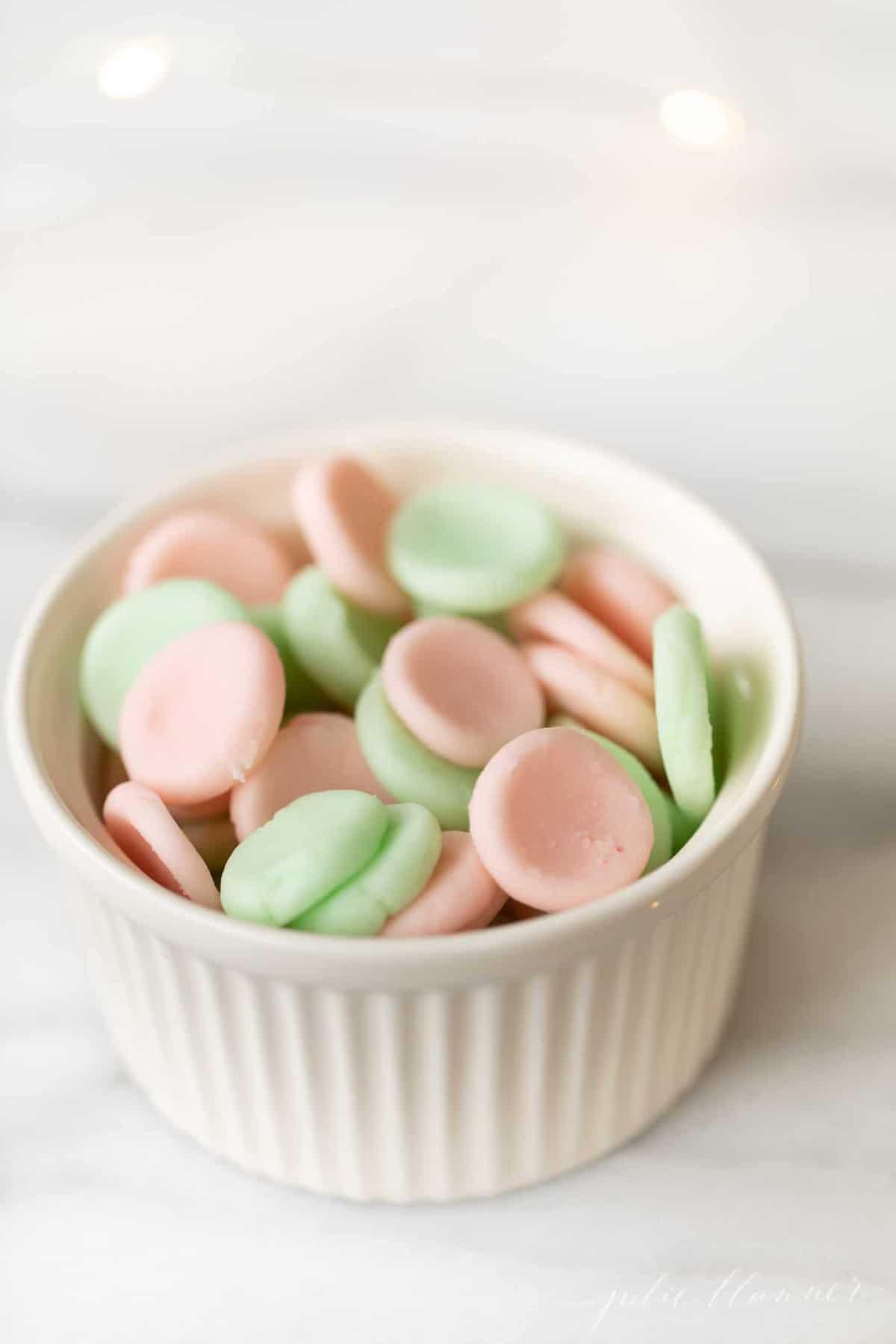 Green an pink candies in a white ramekin