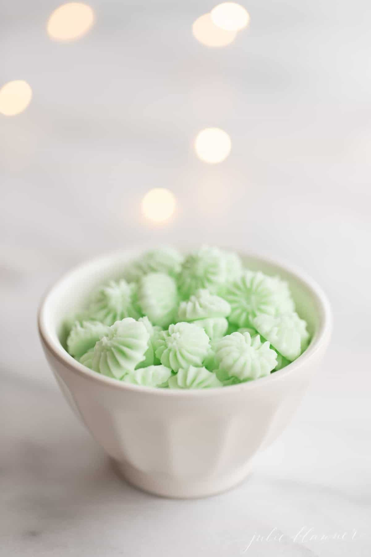 Green cream cheese mints in a small white bowl