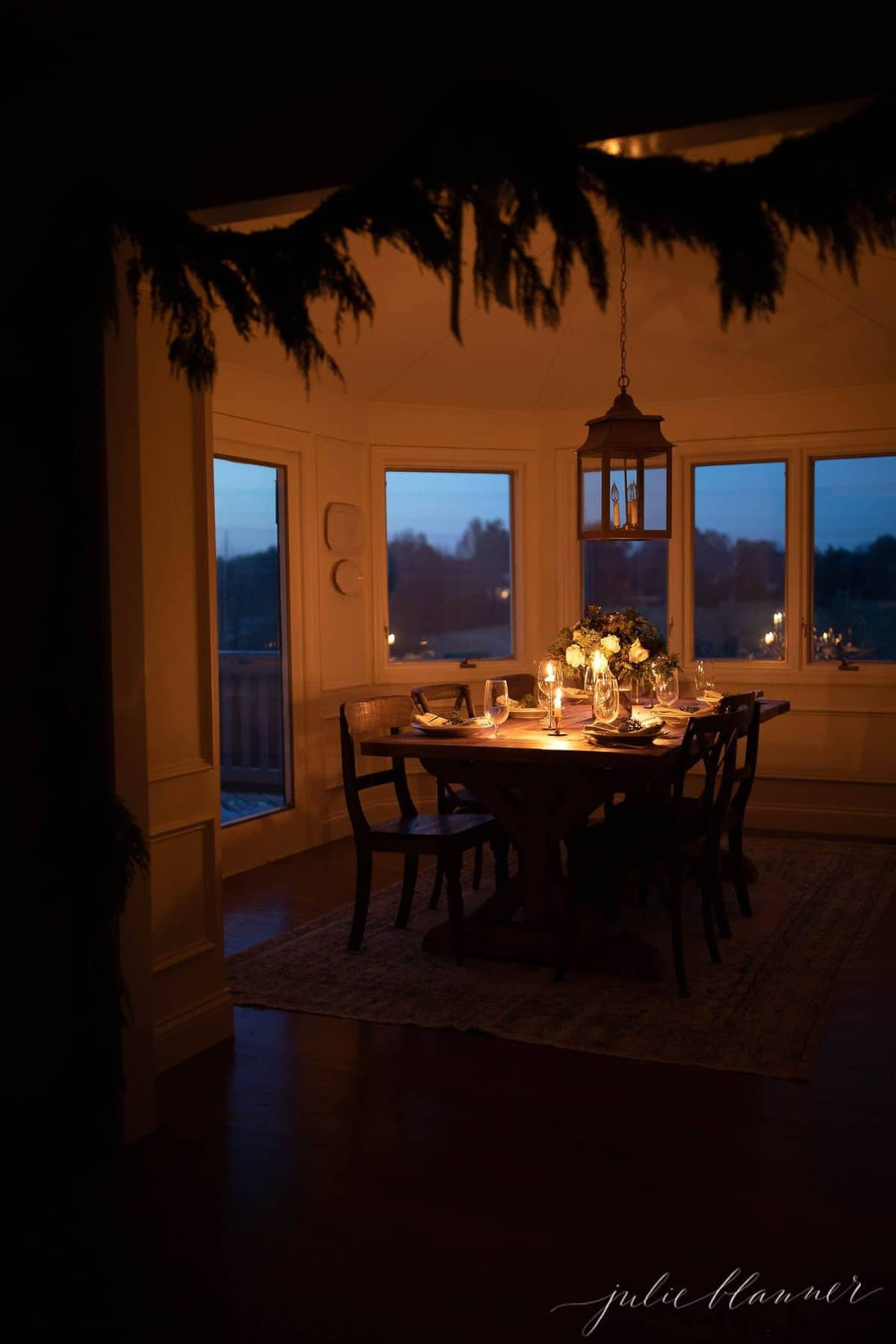 Dining room at night, framed by a garland around the entryway.