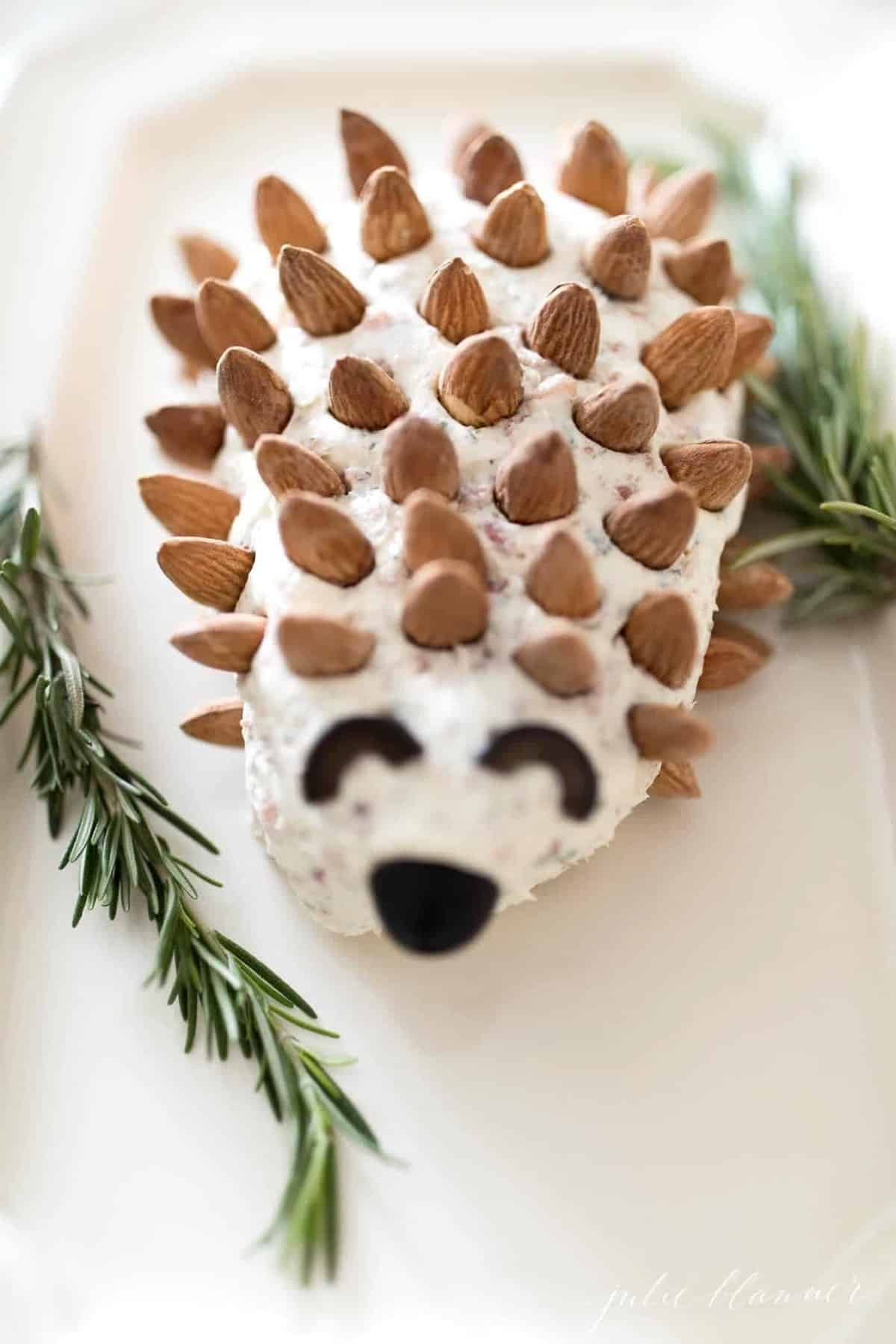 Cheeseball in the shape of a hedgehog on a white platter.