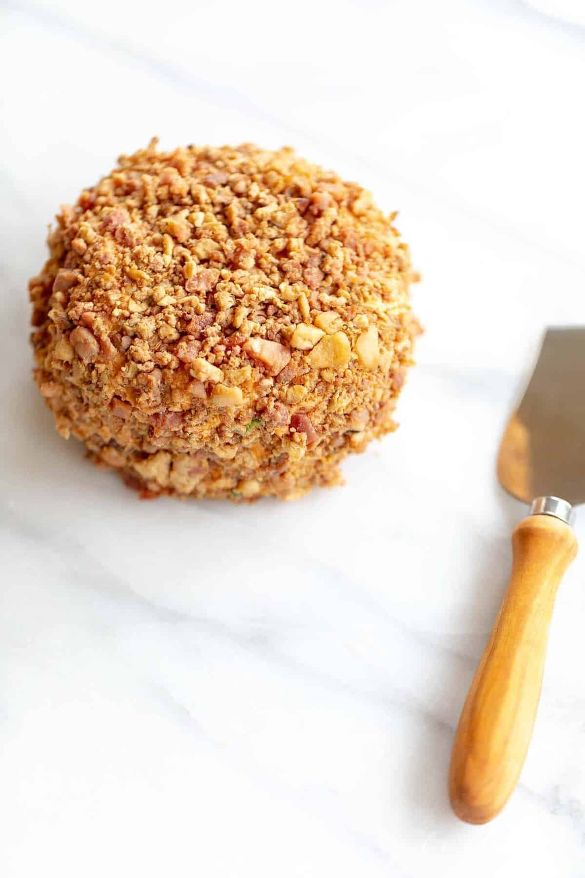 Marble counter top with a bacon covered cheese ball, serving utensil to the side.