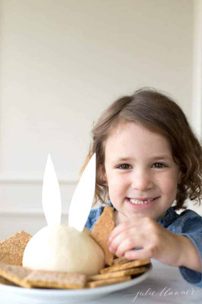 Little girl eating a dessert cheese ball with bunny ears.