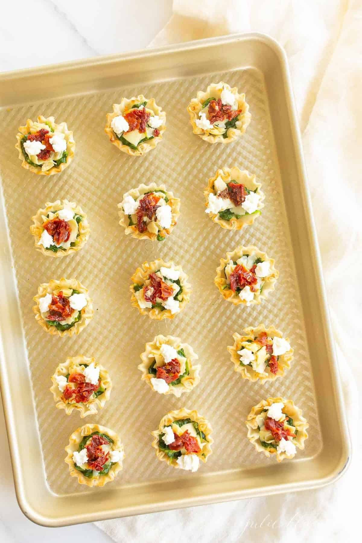 A gold baking sheet with rows of phyllo cup appetizers.