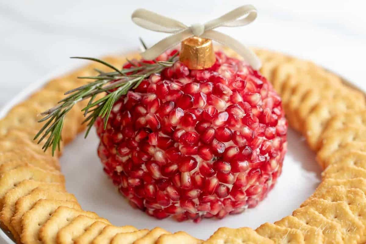 A festive pomegranate cheese ball on a platter with crackers.