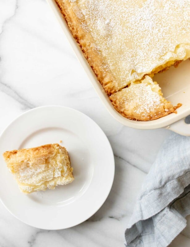 gooey butter cake in baking dish and a slice on a white plate
