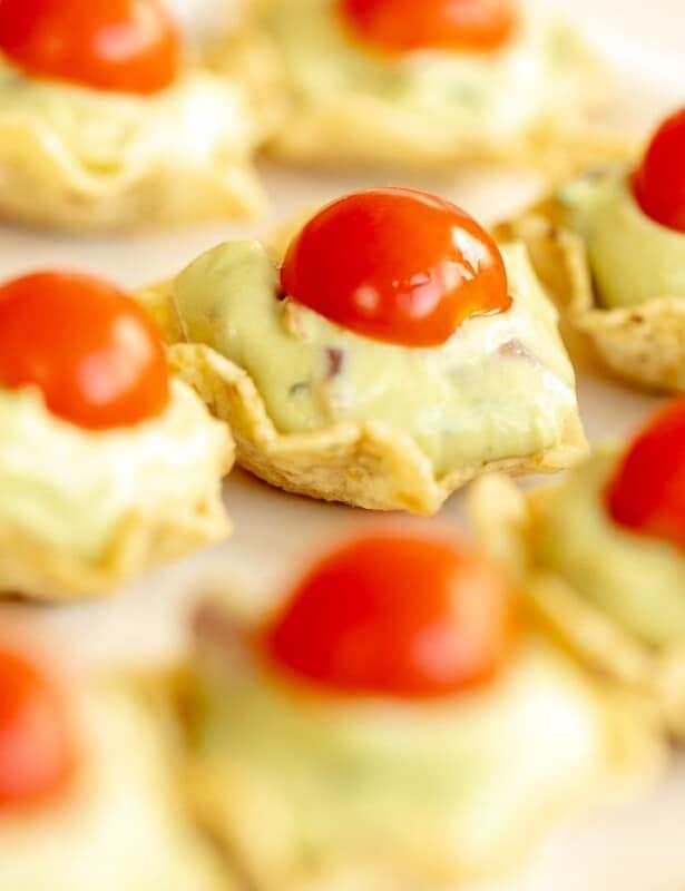 Guacamole bites on a white platter.