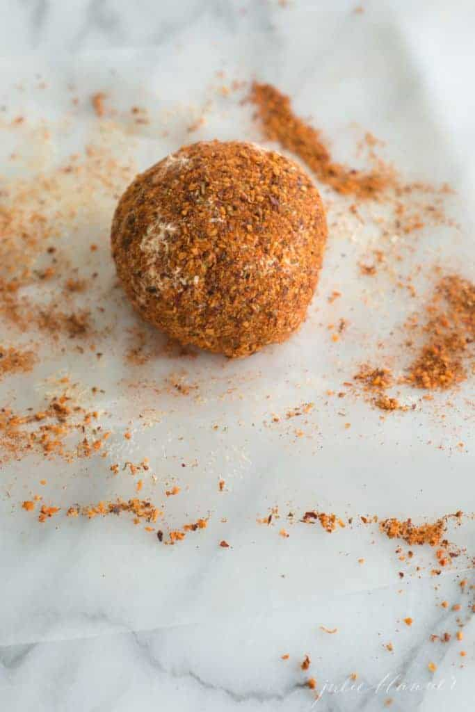 A simple cheeseball covered in spices on a marble surface.
