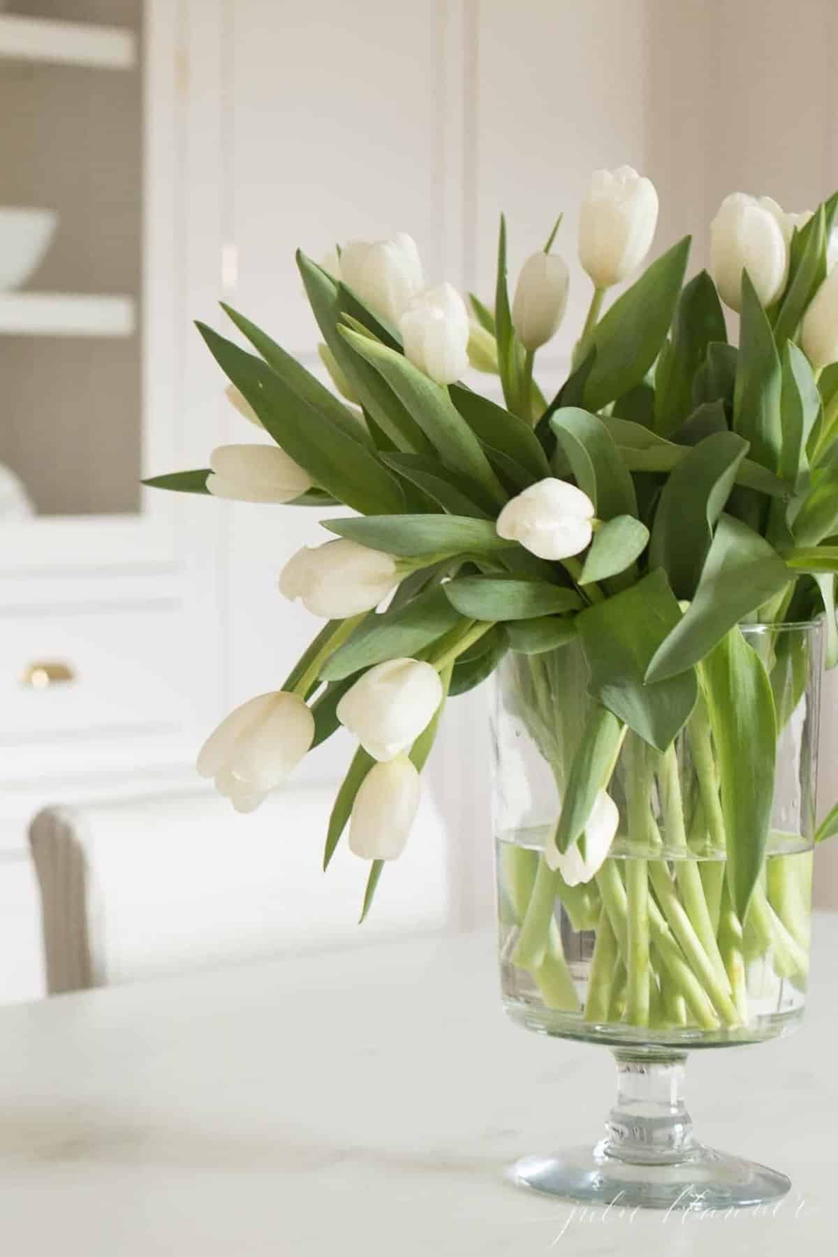 A white kitchen with a clear vase of white tulips.