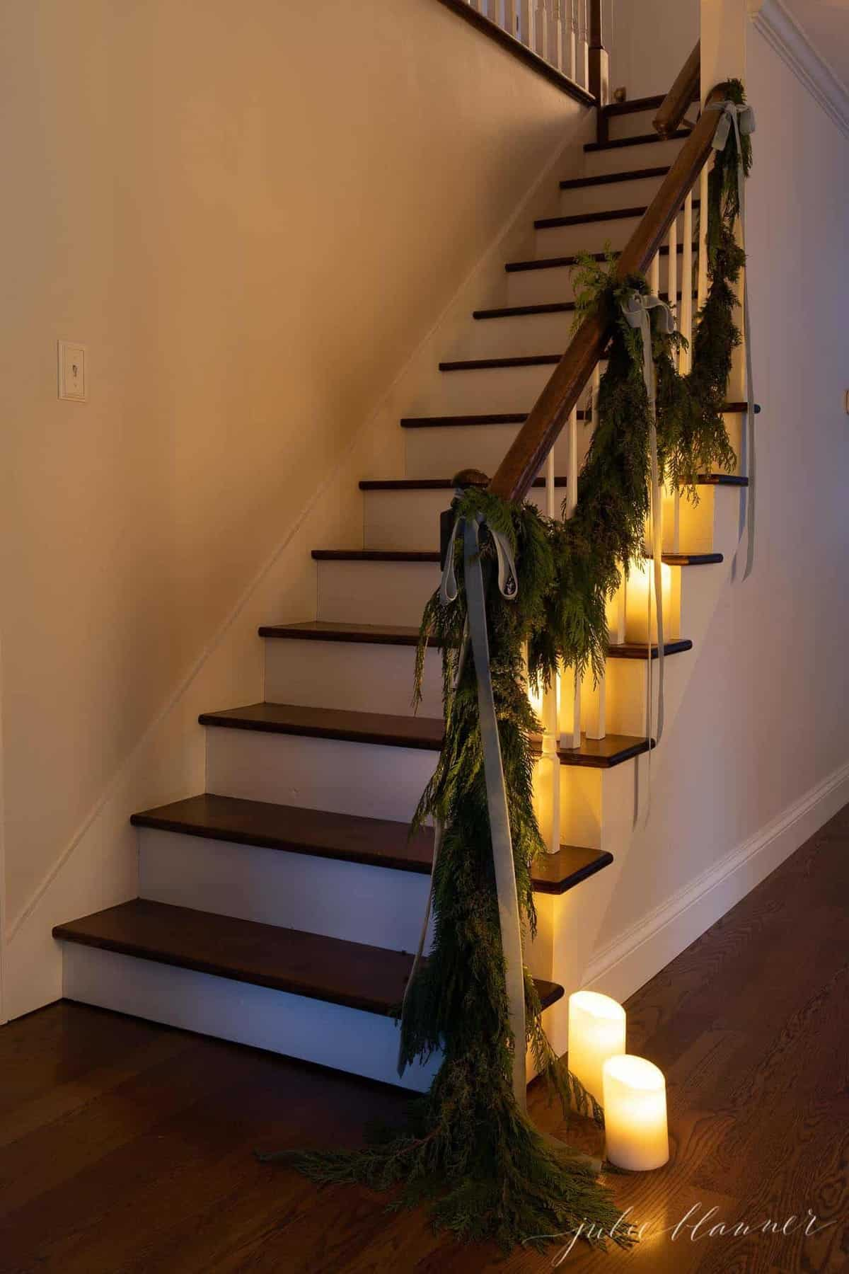White walls, wooden staircase decorated with candles and garland at Christmas.