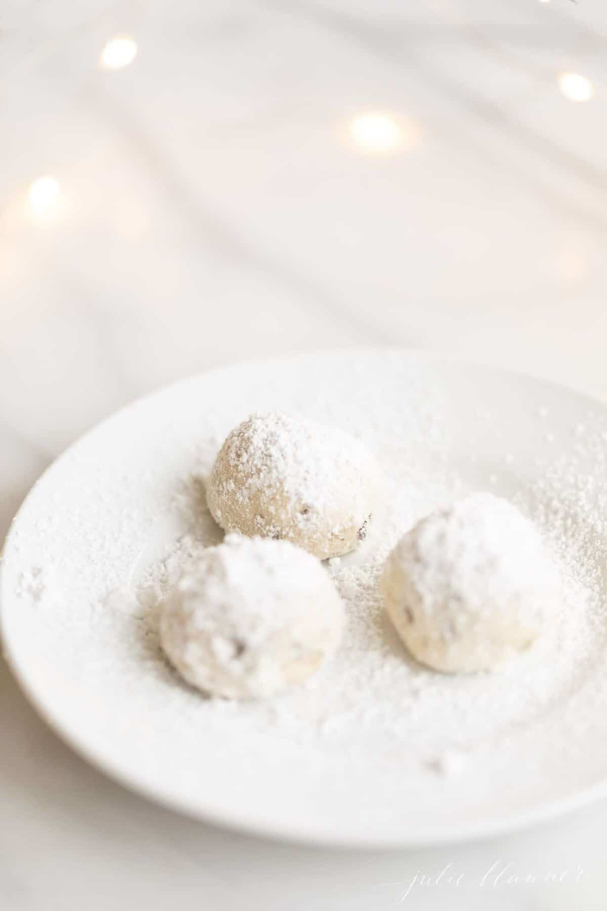 A small white plate with a group of three pecan snowball cookies.
