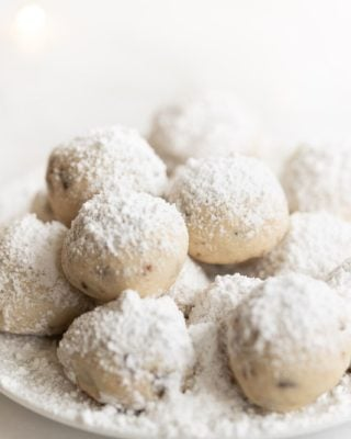 A white plate on a white surface featuring snowball cookies dusted in powdered sugar.