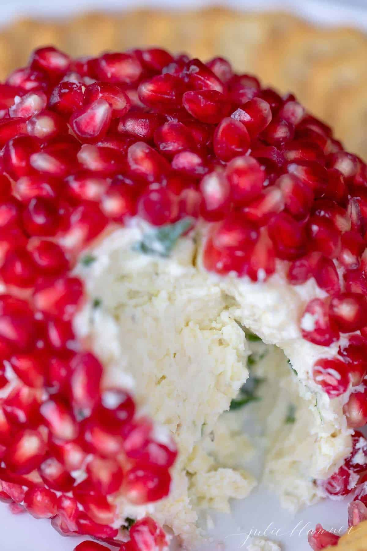 Close up of a pomegranate cheeseball, a slice removed to look inside.